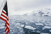 horizontal stock photography | Alaska, Glacier Bay National Park, Ice floes and flag, image id 7-192-12