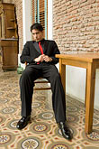 apparel stock photography | Argentina, Buenos Aires, Tango dancer, solo portrait, young man seated, image id S8-451-10460