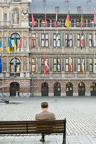 image 8-744-2175 Belgium, Antwerp, Man sitting alone on bench in Grote Markt in front of Town Hall, Stadhuis