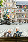 town stock photography | Belgium, Antwerp, Two men on bench in Grote Markt in front of Town Hall, Stadhuis, and Brabo statue, image id 8-744-2177