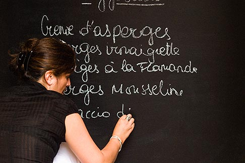 image 8-747-2847 Belgium, Brussels, Woman writing menu on chalk board