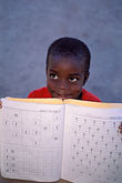 vertical stock photography | Belize, Hopkins Village, Garifuna boy with schoolwork, image id 6-46-33