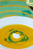 plate setting stock photography | Food, Carrot ginger rosemary soup with sour cream and spinach coulis, image id 4-797-91