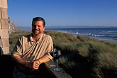 man on beach stock photography | California, Santa Cruz County, Pajaro Dunes, Man relaxing on balcony, image id 5-673-69