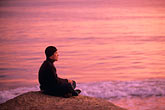 coast stock photography | California, Santa Cruz, Man meditating at sunset, image id 7-600-89