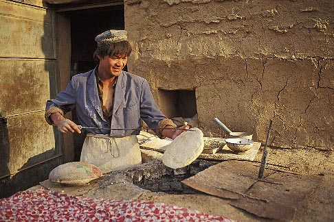 image 4-155-11 China, Turpan, Baker preparing Uighur bread nan