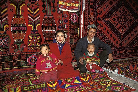 image 4-161-8 China, Turpan, Uighur family selling carpets in bazaar