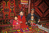horizontal stock photography | China, Turpan, Uighur family selling carpets in bazaar, image id 4-161-8