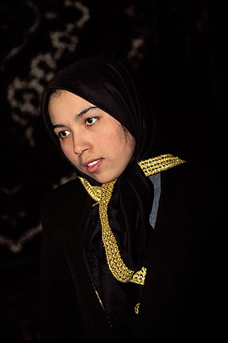 image 4-167-24 China, Urumqi, Uighur woman at carpet stall in bazaar