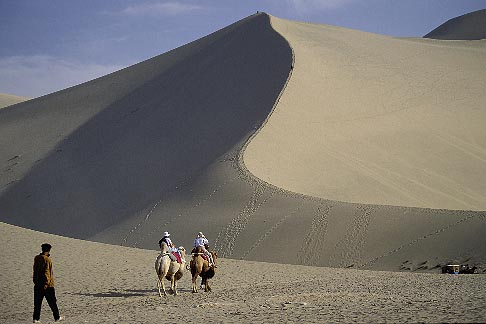 image 4-387-5 China, Dunhuang, Tourist riding camels at the Mingsha sand dunes