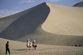 arid stock photography | China, Dunhuang, Tourist riding camels at the Mingsha sand dunes , image id 4-387-5