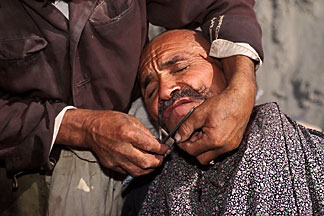 4-416-37  stock photo of China, Kashgar, Getting a shave at the Sunday market