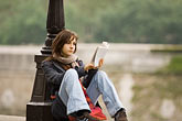 woman seated outside stock photography | France, Paris, Reading on the bank of the Seine, image id 6-450-5841