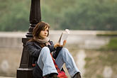 woman seated outside stock photography | France, Paris, Reading on the bank of the Seine, image id 6-450-5842