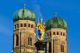 statue stock photography | Germany, Munich, Frauenkirche towers and Mariensaule (St Mary