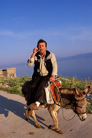 3-701-39  stock photo of Greece, Hydra, Man on donkey with cell phone