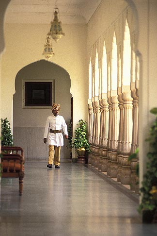 image 7-339-19 India, Jaipur, Man walking in hallway, Rambagh Palace