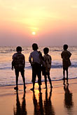 four teenage boys stock photography | India, Trivandrum, Children at sunset, Kovalam Beach, image id 7-57-17