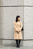 vertical stock photography | Japan, Tokyo, Businesswoman waiting outside office building, image id 5-850-2746