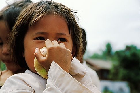 image S3-152-22 Laos, Phon Kham, Young girl eating an apple