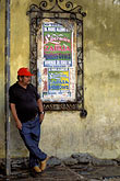 watch out stock photography | Mexico, San Miguel de Allende, Man waiting for bus, with poster, image id 4-293-1