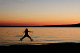 sunset on beach stock photography | Michigan, Lake Superior, Kid jumping on the beach, image id 4-880-1045