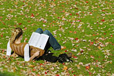 single minded stock photography | Canada, Montreal, McGill University, woman student reading on lawn, image id 6-460-2210