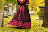 long stock photography | Canada, Montreal, Mount Royal Cemetery, woman with period dress, walking, low angle view, image id 6-460-7501