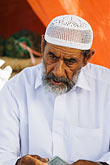 concentration stock photography | Oman, Buraimi, Arab man, seated, with traditional kummah cap, image id 8-730-1832