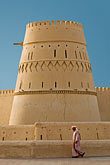 vertical stock photography | Oman, Buraimi, Al Khandaq Fort, with man in traditional dress, walking, image id 8-730-1855