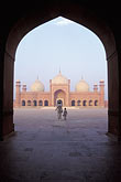 man on the plaza stock photography | Pakistan, Lahore, Archway, early morning, Badshahi Mosque, image id 4-468-13