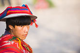 horizontal stock photography | Peru, Ollantaytambo, Young Quechua boy in traditional clothing and hat, with red coven cloth, side view, image id 8-760-1191