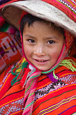 front view stock photography | Peru, Ollantaytambo, Quechua child in traditional clothing and hat, with red woven cloth, front view, image id 8-760-1214