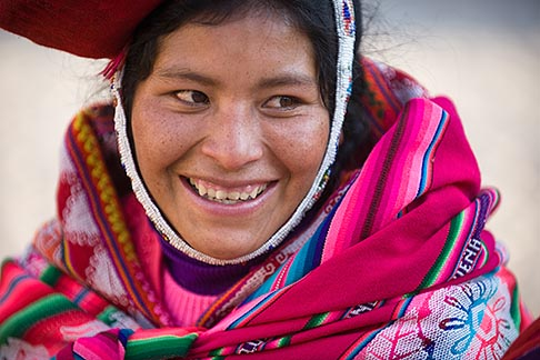 image 8-760-1261 Peru, Ollantaytambo, Smiling Quechua woman in traditional clothing and hat, with red woven cloth, front view