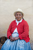 front view stock photography | Peru, Ollantaytambo, Senior Quechua woman, seated outdoors, with hat and red pullover, front view, image id 8-760-1274