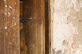 horizontal stock photography | Peru, Ollantaytambo, Woman with peeking from behind half-open wooden door, image id 8-760-1353
