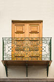 wooden balcony and shuttered window stock photography | Peru, Cuzco, Wrought-iron balcony and wooden-shuttered window, image id 8-761-1110