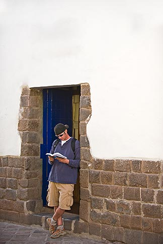 image 8-761-938 Peru, Cuzco, Tourist standing in doorway reading guidebook