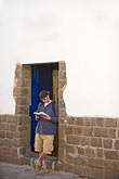 travel stock photography | Peru, Cuzco, Tourist standing in doorway reading guidebook, image id 8-761-938
