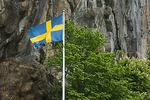 image 5-710-5505 Sweden, Fjallbacka, Swedish flag and cliffside