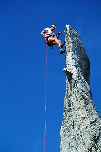 image 2-98-3 Switzerland, Bergell, Climber rappelling on La Fiamma