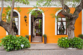 facade stock photography | Uruguay, Colonia del Sacramento, Trees and orange facade of historic building in old town, image id 8-802-4310