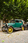 vertical stock photography | Uruguay, Colonia del Sacramento, Green antique automobile parked under tree, image id 8-802-4382