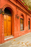 vertical stock photography | Uruguay, Colonia del Sacramento, Arched doorway along cobbled side street , image id 8-802-4398