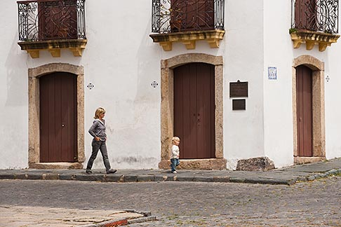 image 8-803-4683 Uruguay, Colonia del Sacramento, Woman walking, cobbled street, Historic District