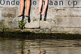 students sitting alongside canal stock photography | Belgium, Ghent, Students sitting alongside canal, legs only, image id 8-742-1799