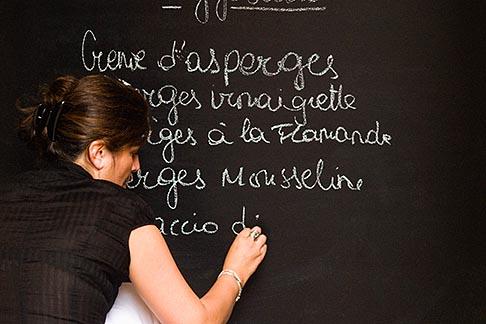 image 8-747-2847 Belgium, Brussels, Woman writing menu on chalk board