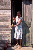 habitat stock photography | Belize, Monkey River, Woman sweeping house steps, image id 6-75-31