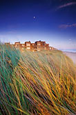 beach with blue water and sky stock photography | California, Santa Cruz County, Pajaro Dunes, Condos and dune grass with full moon, image id 5-672-75