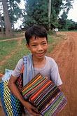 fabric for sale stock photography | Cambodia, Siem Reap, Boy with cloth, Banteay Srei, image id 0-402-15